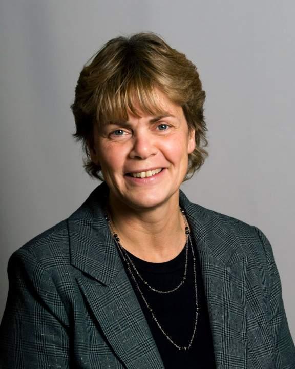 Lerums toppkandidat till Riksdagen, Helena Gellerman, mot en ljusgrå bakgrund. Hon ler och tittar in i kameran. Hon har på sig en mörkgrå kavaj med en svart blus under och ett halsband.